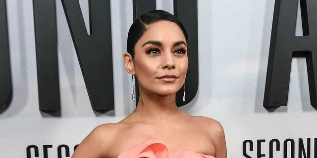 Vanessa Hudgens stunned in a low-cut black swimsuit on Tuesday while standing in the snow.
