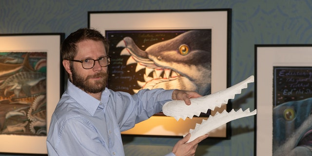 Idaho Museum of Natural History Director Leif Tapanila holds a replica of theEdestus' sharp-toothed jaw.