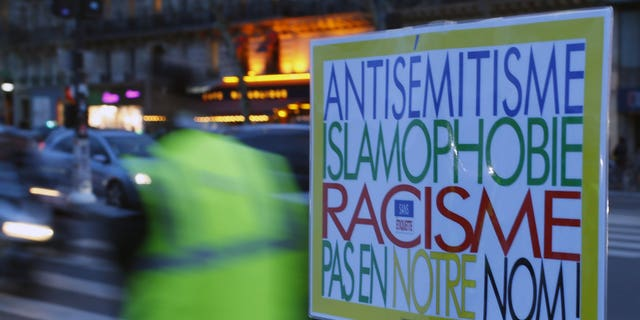 """A poster reading """"Anti-Semitism, Islamophobia, Racism, Not in Our Name"""" during a gathering decrying anti-Semitism at Place de la Republique in Paris, Monday, Feb. 18, 2019 amid an upsurge in anti-Semitism in France."""