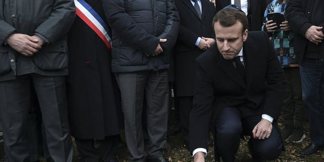 French President Emmanuel Macron puts a stone on a vandalized grave in a show of respect during a visit at the Jewish cemetery in Quatzenheim, eastern France, Tuesday Feb. 19, 2019. French residents and public officials from across the political spectrum geared up Tuesday for nationwide rallies against anti-Semitism following a series of anti-Semitic acts, including the swastikas painted on about 80 gravestones at the Jewish cemetery overnight.