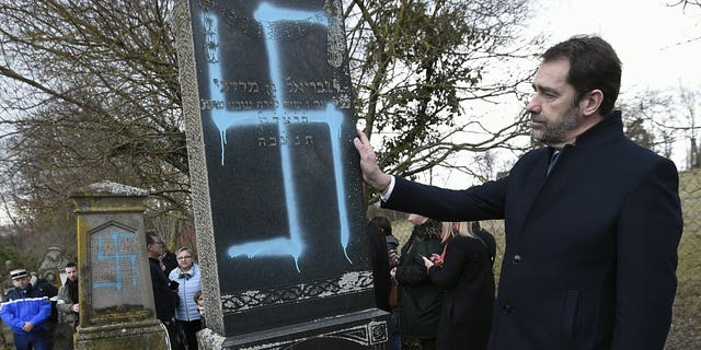 French Interior Minister Christophe Castaner touches a vandalized tombstone at the Jewish cemetery of Quatzenheim, eastern France, Tuesday Feb. 19, 2019. French residents and public officials from across the political spectrum geared up Tuesday for nationwide rallies against anti-Semitism following a series of anti-Semitic acts, including the swastikas painted on about 80 gravestones at the Jewish cemetery overnight.