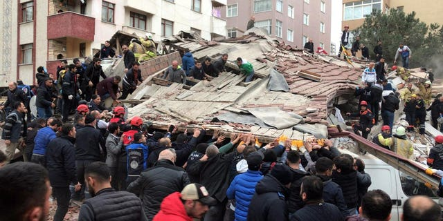 Rescue workers and people try to remove debris of a seven-story building which collapsed in Istanbul, Wednesday, Feb. 6, 2019. A seven-story building collapsed in Istanbul on Wednesday, killing at least one person and trapping several others inside the rubble, Turkish media reports said.