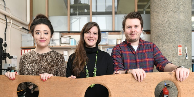 Museum of London staff Maddie Hammond, Emily Brazee and Tom Kelly pictured with a replica of a 12th century triple toilet seat, before it goes on display as part of the Secret Rivers exhibition.
