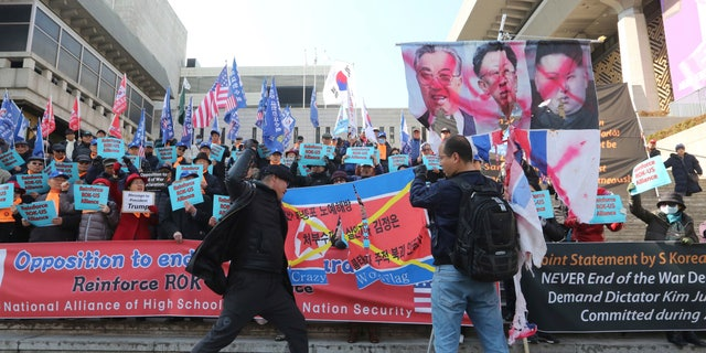 A South Korean protester with a box cutter tears a North Korean flag during a rally to oppose end of the Korean War declaration in the upcoming summit between U.S. President Donald Trump and North Korean leader Kim Jong Un near the U.S. embassy in Seoul, South Korea, Tuesday, Feb. 26, 2019. (AP Photo/Ahn Young-joon)