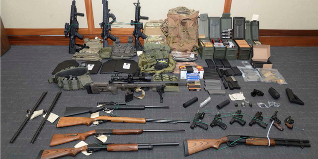 "This image provided by the U.S. District Court in Maryland shows a photo of firearms and ammunition that was in the motion for detention pending trial in the case against Christopher Paul Hasson. Prosecutors say that Hasson, a Coast Guard lieutenant is a ""domestic terrorist"" who wrote about biological attacks and had a hit list that included prominent Democrats and media figures. He is due in court on Feb. 21 in Maryland. Prosecutors say Hasson espoused extremist views for years. Court papers say Hasson described an ""interesting idea"" in a 2017 draft email that included ""biological attacks followed by attack on food supply."" (U.S. District Court via AP)"