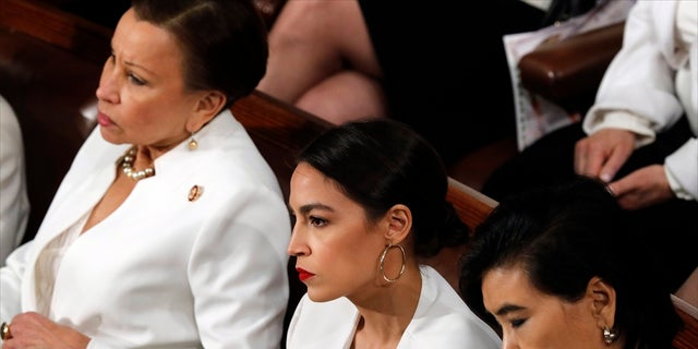 Rep. Alexandria Ocasio-Cortez, D-N.Y., center, listens as President Trump delivers his State of the Union address to a joint session of Congress on Capitol Hill in Washington, Tuesday, Feb. 5, 2019. (AP Photo/J. Scott Applewhite)