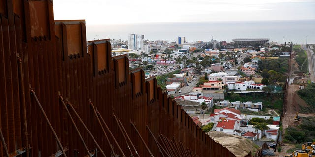 In this Jan 15, 2019 image, a section of newly-replaced border wall separates Tijuana, Mexico, above left, from San Diego, right, in San Diego. Border Patrol officials say some Mexican homes and structures encroach on U.S. soil posing a dilemma for authorities when replacing the wall. [AP Photo/Gregory Bull)