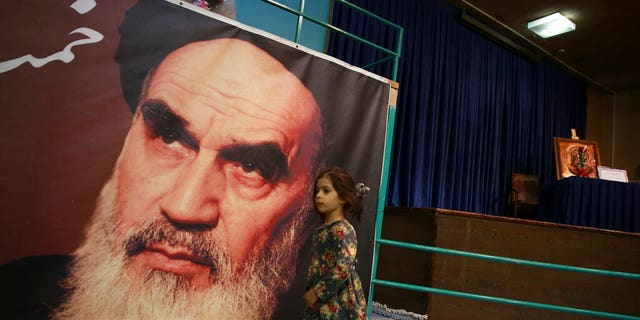 In this Tuesday, Jan. 22, 2019, photo, a girl walks past a poster of Ayatollah Ruhollah Khomeini, at a mosque where he made speeches, in northern Tehran, Iran. The memory of Khomeini, who died in 1989 at the age of 86, looms large over Tehran today. His image is on bank notes and in textbooks in Iran, often as an embodiment of the 1979 Islamic Revolution that swept aside the country's shah and forever changed the nation.