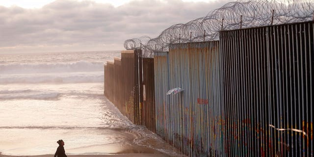 """FILE - In this Jan. 9, 2019 file photo, a woman walks on the beach next to the border wall topped with razor wire in Tijuana, Mexico. What started as an online fundraiser to provide President Donald Trump with donations for his southern border wall has morphed into a new foundation whose members vow to build a wall themselves. The """"We The People Will Build the Wall"""" campaign has surpassed $20 million since it was created in December by Air Force veteran and triple amputee Brian Kolfage. The campaign has received almost 350,000 donations even as wall opponents derided the effort and after the longest government shutdown in U.S. history ended with Congress refusing Trump's demand for billions in wall funding. (AP Photo/Gregory Bull, File)"""