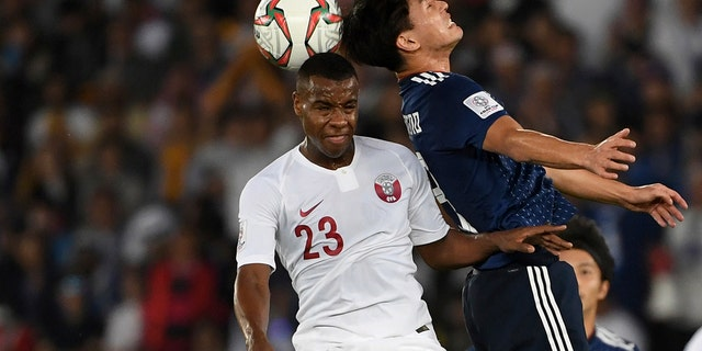 Japan's forward Takumi Minamino, right, challenges Qatar's defender Assim Madibo, left, during the AFC Asian Cup final match between Japan and Qatar in Zayed Sport City in Abu Dhabi, United Arab Emirates, Friday, Feb. 1, 2019.