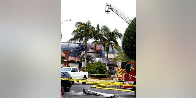 Firefighters work the scene of a deadly plane crash in the residential neighborhood of Yorba Linda, Calif.