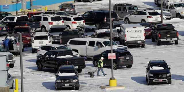 A worker walks across a snow-covered parking lot, Tuesday, Feb. 5, 2019, at Seattle-Tacoma International Airport in Seattle. (Associated Press)