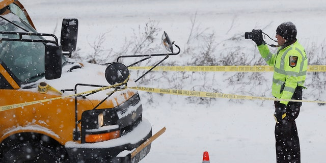 The driver of a school bus was taken to the hospital in a shooting on HWY 35 near downtown Minneapolis, Tuesday, Feb. 5, 2019. Authorities say a school bus driver was wounded in a shooting that followed a crash with another vehicle on a snowy interstate near downtown Minneapolis. (Richard Tsong-Taatarii/Star Tribune via AP)