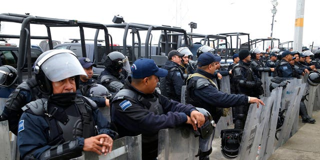 "Mexican Federal Police in riot gear guard outside of a migrant shelter for Central American immigrants in Piedras Negras, Mexico, Tuesday, Feb. 5, 2019. A caravan of about 1,600 Central American migrants camped Tuesday in the Mexican border city of Piedras Negras, just west of Eagle Pass, Texas. The governor of the northern state of Coahuila described the migrants as ""asylum seekers,"" suggesting all had express intentions of surrendering to U.S. authorities. (Jerry Lara/The San Antonio Express-News via AP)"