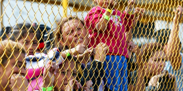 "Central American immigrant families look out through the fence of a shelter in Piedras Negras, Mexico, Tuesday, Feb. 5, 2019. A caravan of about 1,600 Central American migrants camped Tuesday in the Mexican border city of Piedras Negras, just west of Eagle Pass, Texas. The governor of the northern state of Coahuila described the migrants as ""asylum seekers,"" suggesting all had express intentions of surrendering to U.S. authorities. (Jerry Lara/The San Antonio Express-News via AP)"