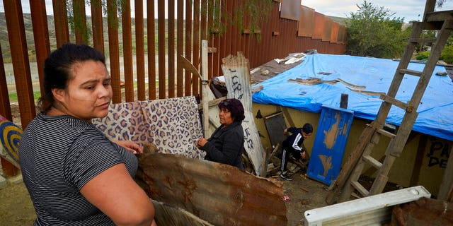 FILE - In this Jan. 16, 2019, file photo, Yuli Arias, left, stands near a newly-replaced section of the border wall as her mother, Esther Arias, center, stands in the family's house that was once threatened by construction along the border in Tijuana, Mexico. The Trump administration said Thursday, Feb. 7, 2019, it would waive environmental reviews to replace up to 14 miles [22.5 kilometers) of border barrier in San Diego, shielding itself from potentially crippling delays. (AP Photo/Gregory Bull, File)