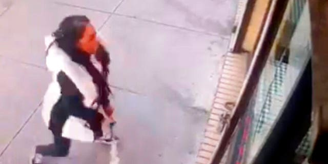 "A woman smashes the windows of ""Back Home Restaurant"" in the Bronx borough of New York."