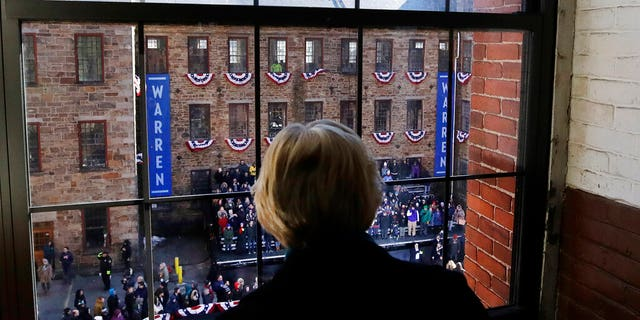 Sen. Elizabeth Warren, D-Mass., looks out a window at Everett Mills as a crowd gathers for an event where she formally launched her presidential campaign, Saturday, Feb. 9, 2019, in Lawrence, Mass. (AP Photo/Elise Amendola)