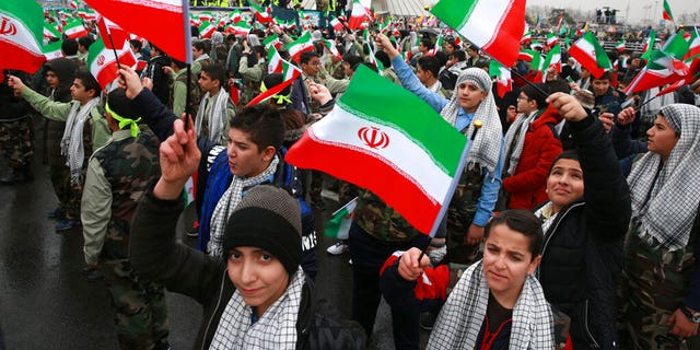 Children wave Iranian flags during a ceremony celebrating the 40th anniversary of the Islamic Revolution, at the Azadi, Freedom, Square in Tehran, Iran, Monday, Feb. 11, 2019.