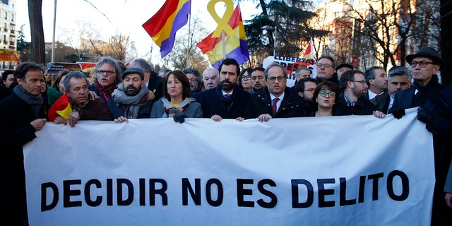 "The president of Catalonian Parliament, Roger Torrent, center, and the Catalan regional President Quim Torra, center right, hold a placard that reads in Spanish: "" To Choose is not a Crime"", outside the Spanish Supreme Court in Madrid."