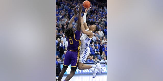 Kentucky's PJ Washington, right, shoots while pressured by LSU's Naz Reid, left, during the second half of an NCAA college basketball game in Lexington, Ky., Tuesday, Feb. 12, 2019. LSU won 73-71. (AP Photo/James Crisp)