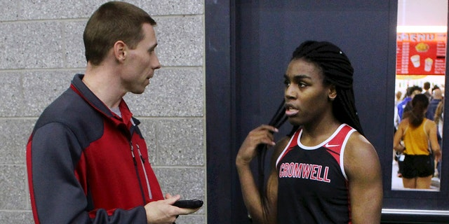 In this Thursday, Feb. 7, 2019 photo, Cromwell High School track coach Brian Calhoun, left, speaks to transgender athlete Andraya Yearwood during a break at a meet at Hillhouse High School in New Haven, Conn. Yearwood, a 17-year-old junior at Cromwell High School, is one of two transgender high school sprinters in Connecticut, transitioning to female. (AP Photo/Pat Eaton-Robb)