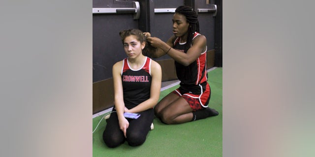 In this Thursday, Feb. 7, 2019 photo, Cromwell High School transgender athlete Andraya Yearwood , right, braids the hair of teammate Taylor Santos, left, during a break at a track meet at Hillhouse High School in New Haven, Conn. Yearwood, a 17-year-old junior at Cromwell High School, is one of two transgender high school sprinters in Connecticut, transitioning to female. (AP Photo/Pat Eaton-Robb)
