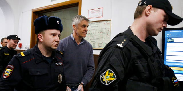 Founder of the Baring Vostok investment fund Michael Calvey, center, is escorted to the court room in Moscow, Russia, Friday, Feb. 15.