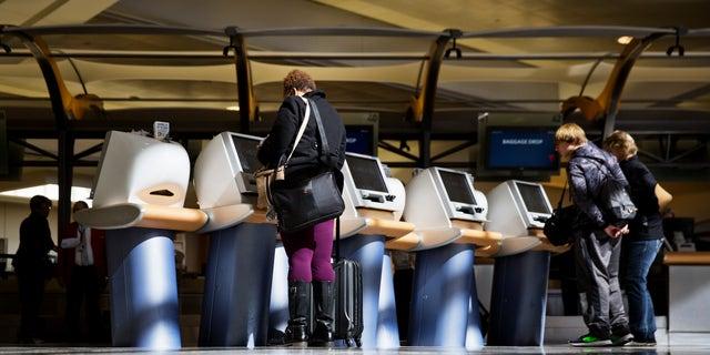 Passengers check in for Delta Air Lines flights at kiosks at Hartsfield-Jackson Atlanta International Airport in Atlanta, Jan. 30, 2017. (Associated Press)
