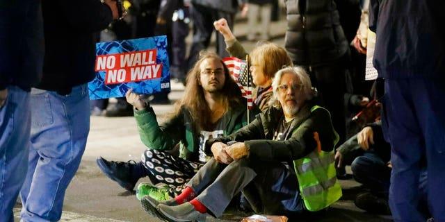 Protesters of President Donald Trump's national emergency declaration block traffic near Trump International Hotel & Tower on Friday, Feb. 15, 2019, in New York. (AP Photo/Frank Franklin II)