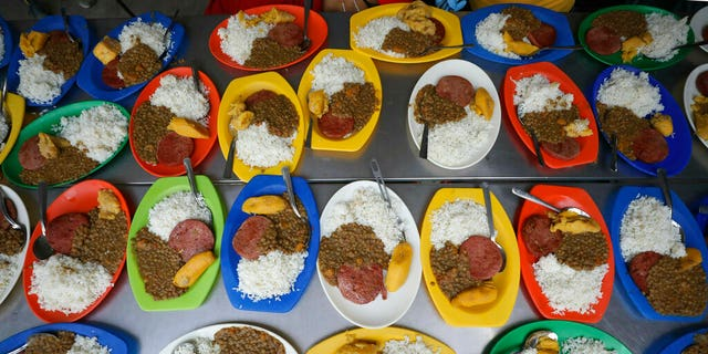 Free lunches prepped with lentils, a slice of bologna, rice and a piece of plantain ready to be served at a migrant shelter in La Parada, near Cucuta, Colombia, on the border with Venezuela, Monday. (AP Photo/Fernando Vergara)