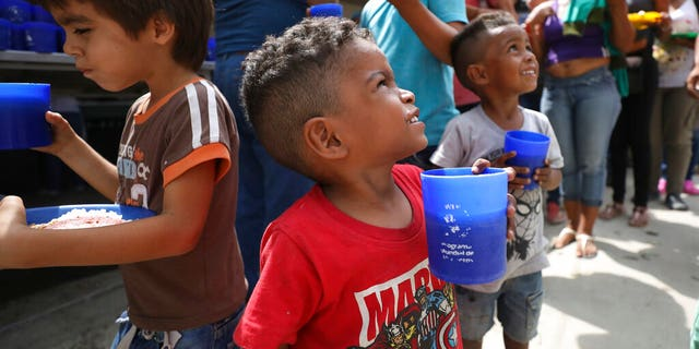 "Venezuelan boys holding cups of a grape-flavored drink, part of the free lunch that is given out daily at the ""Divina Providencia"" migrant shelter in La Parada, near Cucuta, Colombia, on the border with Venezuela, on Monday. (AP Photo/Fernando Vergara)"