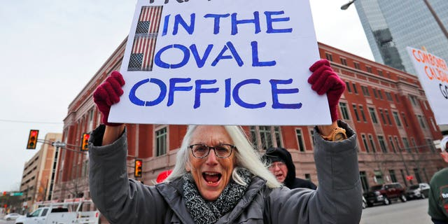 Cathy Clark holding a sign during a protest in downtown Fort Worth, Texas, on Monday. (AP Photo/LM Otero)