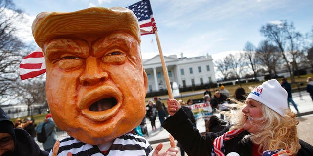 A person dressed to look like President Donald Trump in a prison uniform, and others gather Monday, Feb. 18, 2019, in front of the White House in Washington, to protest that President Donald Trump declared a national emergence along the southern boarder. (AP Photo/Carolyn Kaster)