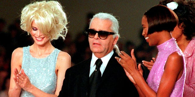 Karl Lagerfeld is applauded by Claudia Schiffer, left, and Naomi Campbell at the end of the Chanel 1997 Spring-Summer ready-to-wear collection presented in Paris.