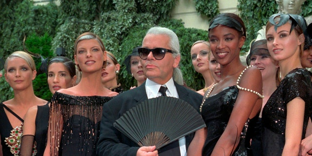 Karl Lagerfeld surrounded by Canadian model Linda Evangelista, left, and British model Naomi Campbell, right, and other models after the presentation of his 1996-97 fall-winter haute couture fashion collection for Chanel in Paris, on July 9, 1996. (AP Photo/Lionel Cironneau, File)