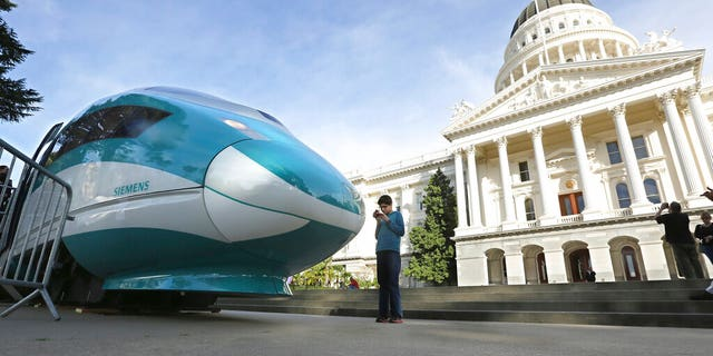 FILE - In this Feb. 26, 2015, file photo, a full-scale mock-up of a high-speed train is displayed at the Capitol in Sacramento, Calif. The Trump administration plans to cancel $929 million in U.S. money for California's beleaguered high-speed rail project and wants the state to return an additional $2.5 billion it's already spent. The U.S. Department of Transportation announcement Tuesday, Feb. 19, 2019, came after President Donald Trump last week threatened to make California pay back the money awarded to build the train between Los Angeles and San Francisco. (AP Photo/Rich Pedroncelli, File)