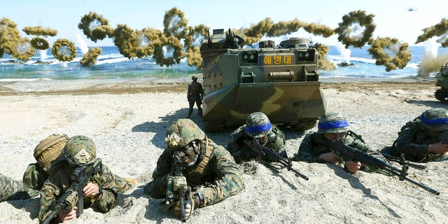 Marines of the U.S., left, and South Korea, wearing blue headbands on their helmets, taking positions after landing on a beach during a joint military exercise in 2016. (Kim Jun-bum/Yonhap via AP, File)