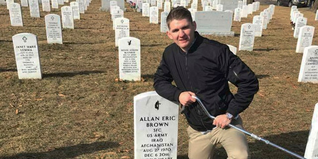 In this Jan. 30, 2018, photo provided by Vicki Hencely, her son Army Spc. Winston Hencely poses for a photo with his service dog at Arlington National Cemetery in Arlington, Va. Hencely, a U.S. soldier grievously wounded in a suicide bombing two years ago in Afghanistan, filed suit Wednesday, Feb. 20, 2019, against an American defense contractor that employed the bomber, saying it failed to supervise the man as he built an explosive vest on the job using the company's tools and parts. (Vicki Hencely via AP)
