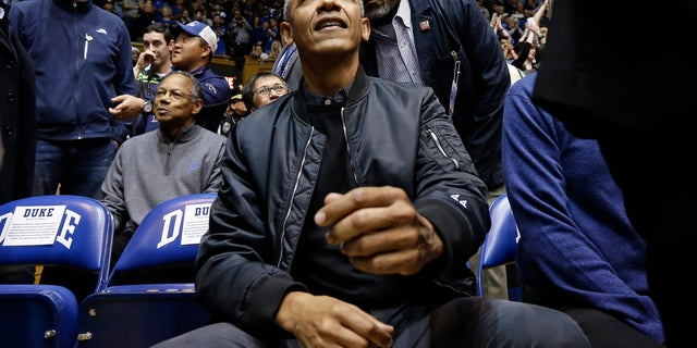 Former President Barack Obama joins fans during an NCAA college basketball game between Duke and North Carolina in Durham, N.C., Wednesday, Feb. 20, 2019. (AP Photo/Gerry Broome)