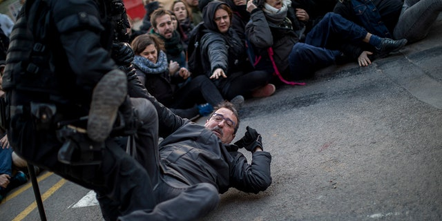 Authorities said one protester was arrested for allegedly hitting a police officer in downtown Barcelona, while a second person was arrested on a highway north of the city where protesters burned tires and threw rocks at a line of riot police.