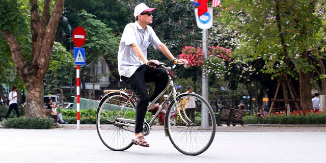 An elderly man rides a bicycle along national flags of Vietnam, North Korea and the United States on Hanoi Street, Viet Nam, Thursday US President Donald Trump and North Korean leader Kim Jong Un will meet at their second summit in Hanoi on the 27th, February 28.