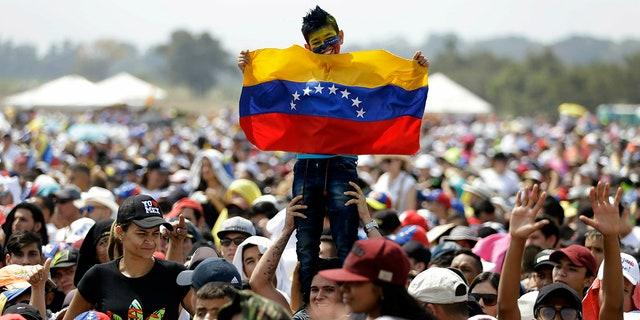A child holds a Venezuelan flag during the Venezuela Aid Live concert on the Colombian side of Tienditas International Bridge on the outskirts of Cucuta, Colombia, on the border with Venezuela, Friday, Feb. 22, 2019. (AP Photo/Fernando Vergara)