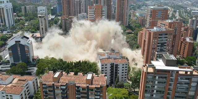 Clouds of dust rise from the implosion of a six-floor apartment building that former cartel boss Pablo Escobar once called home, in Medellin, Colombia, Friday, Feb. 22, 2019. Mayor Federico Gutierrez had been pushing to raze the building and erect in its place a park honoring the thousands of victims, including four presidential candidates and some 500 police officers, killed by Escobar's army of assassins during the Medellin cartel's heyday in the 1980s and 1990s. (AP Photo/Luis Benavidez)