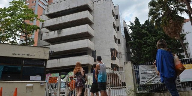 """People look at the six-floor apartment building that former cartel boss Pablo Escobar once called home, in Medellin, Colombia, Friday, Feb. 22, 2019. The white concrete building in Medellin's leafy Poblado neighborhood was gutted by a car bomb in 1988 and has remained an unoccupied eyesore ever since, drawing mostly foreign tourists who sign up every day for tours of Escobar's former hometown haunts. The Netflix """"Narcos"""" series has also popularized such attractions. It was demolished on Friday. (AP Photo/Luis Benavidez)"""