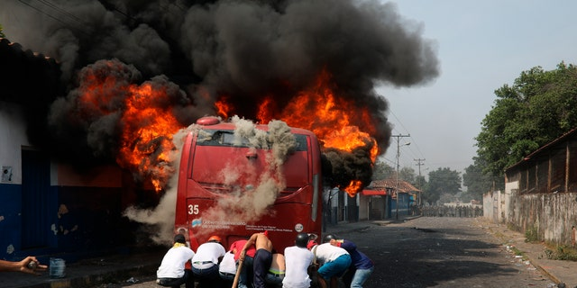 Demonstrators push a bus that was torched during clashes with the Bolivarian National Guard in Urena, Venezuela