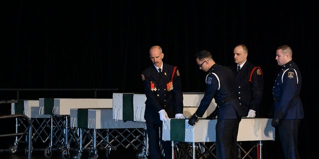 Members of the Halifax Fire and Police honor guard prepare to transport the caskets of the seven Barho children during the funeral for the Syrian refugees in Halifax, Nova Scotia, Canada, on Saturday, Feb. 23, 2019. (Darren Calabrese/The Canadian Press via AP)