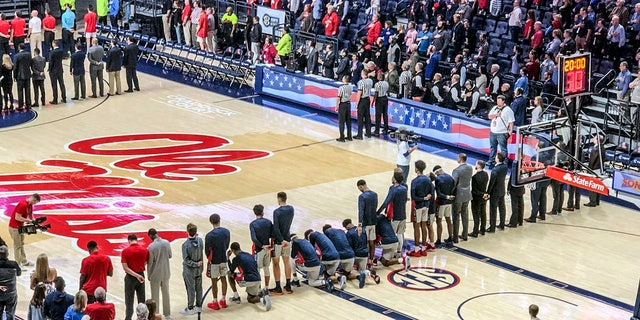 Several University of Mississippi basketball players take a knee during the national anthem before an NCAA college basketball game against Georgia in Oxford, Miss., on Saturday.