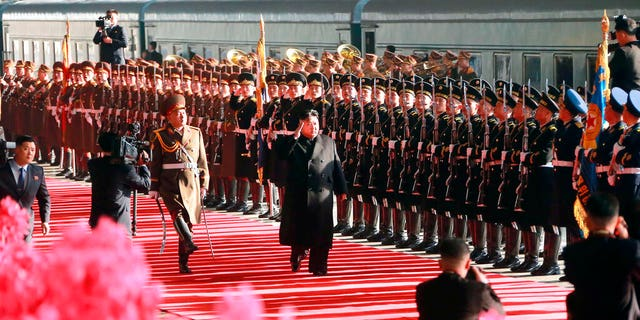 """In this Saturday, Feb. 23, 2019, photo provided on Sunday, Feb. 24, 2019, by the North Korean government, North Korean leader Kim Jong Un salutes while reviewing troops at Pyongyang Station, North Korea, before leaving for Vietnam. Kim was on a train Sunday to Vietnam for his second summit with U.S. President Donald Trump, state media confirmed. Independent journalists were not given access to cover the event depicted in this image distributed by the North Korean government. The content of this image is as provided and cannot be independently verified. Korean language watermark on image as provided by source reads: """"KCNA"""" which is the abbreviation for Korean Central News Agency. (Korean Central News Agency/Korea News Service via AP)"""