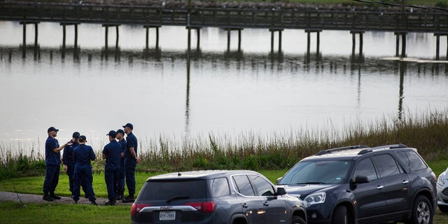 Local and federal officials gather at a space during the investigation of a plane crash in Trinity Bay in Anahuac, Texas, Saturday, February 23, 2019. (Brett Coomer / Houston Chronicle via AP )